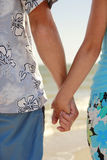 Hands in love couple holding hands on the sea shore Royalty Free Stock Photos
