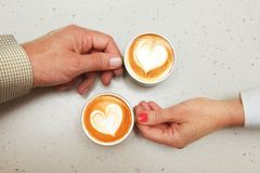 Lovers with cups of coffee stock photography