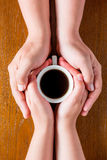 Hands loving couple and a cup of hot coffee Stock Images