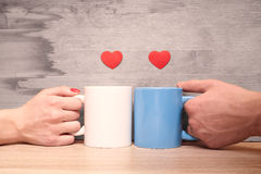 Hands loving couple holding cups with hearts Stock Photo
