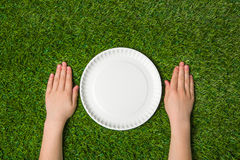 Hands lying near empty paper plate on green grass Royalty Free Stock Photography