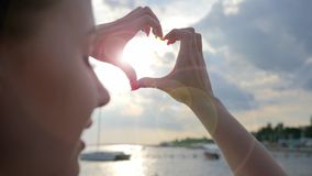 Hands made heart shape at sunset on sea in summer, beautiful woman making love symbol. On background evening sunset in embankment, love to relax at sea stock footage