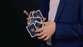 The hands of the magician show a trick with playing cards stock footage