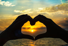 Hands make heart at sunset Royalty Free Stock Image