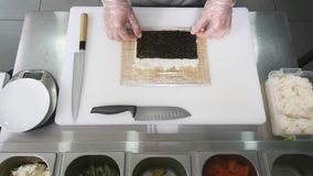 Hands make long sushi roll. Sushi chef demonstrating skill. Famous japanese dish. top view Stock Photos