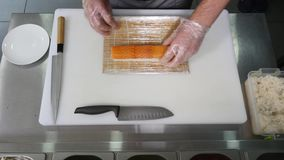 Hands make long sushi roll. Sushi chef demonstrating skill. Famous japanese dish. top view Stock Images
