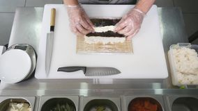 Hands make long sushi roll. Sushi chef demonstrating skill. Famous japanese dish. top view Royalty Free Stock Image