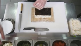 Hands make long sushi roll. Sushi chef demonstrating skill. Famous japanese dish. top view stock footage