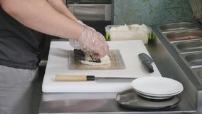 Hands make long sushi roll. Sushi chef demonstrating skill. Famous japanese dish. top view stock video