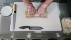 Hands make long sushi roll. Sushi chef demonstrating skill. Famous japanese dish. top view stock video footage