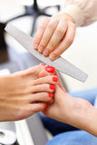 Hands make pedicure by nail files for client Royalty Free Stock Photo