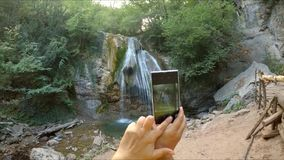 Hands make a photo of a waterfall on the phone. stock video