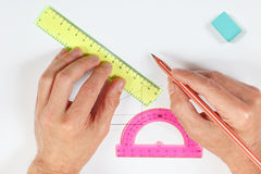Hands making a drawing with pencil and ruler on white sheet of paper Royalty Free Stock Image