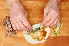 Hands making duck pancakes stock photography