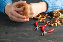 Hands making handcrafted wood earrings, close up stock images