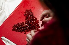 Hands making heart in front of pomegranate seeds on the red cutting board stock photo
