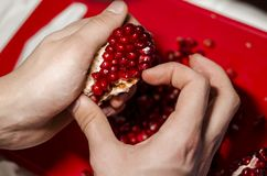 Hands making a heart of pomegranate pieces on the red cutting board stock photo