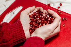 Hands making a heart of pomegranate seeds on the red cutting board stock photos