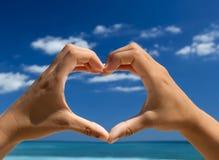 Hands making a heart shape. Female hand making a heart shape against a beautiful blue sky Stock Photography