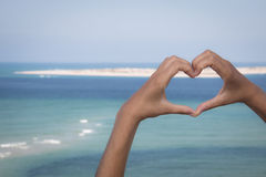 Hands making a heart sign at the beach Royalty Free Stock Image