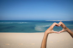 Hands making a heart sign at the beach Royalty Free Stock Photos