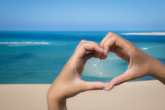 Hands making a heart sign at the beach Stock Images