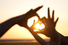 Hands making hearts. Heart shape made of hands putting together against sunset. Silhouette hand gesture of love during sunset Stock Image