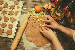 Making gingerbread cookies for Christmas. Hands making homemade gingerbread cookies for Christmas in home kitchen royalty free stock image