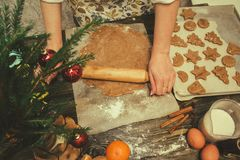 Making gingerbread cookies for Christmas. Hands making homemade gingerbread cookies for Christmas in home kitchen royalty free stock photography