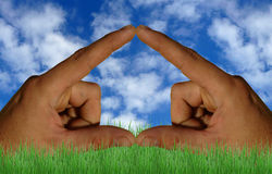 Hands making a house. A picture of two hands making a house with a cloudy blue sky background Royalty Free Stock Photos