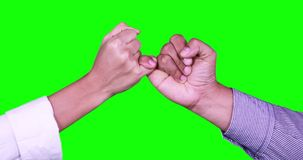 Hands making a pinkie promise. Two anonymous people hands making a pinkie promise in front of green screen background. Shot in 4k resolution