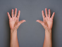 Hands making raise hands up on gray background royalty free stock photo