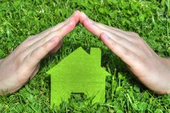 Hands are making roof on top of the house icon standing on the grass Royalty Free Stock Image