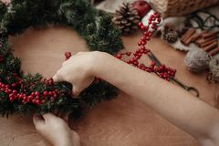Hands making rustic christmas wreath with fir branches, red berries,pine cones,rope, scissors, cinnamon, cotton on rustic wooden. Background. Atmospheric moody stock photo