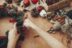 Hands making rustic christmas wreath with fir branches, red berries,pine cones,rope, scissors, cinnamon, cotton on rustic wooden. Background. Atmospheric moody royalty free stock images