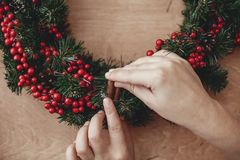 Hands making rustic christmas wreath, holding cinnamon at fir br. Anches, red berries , pine cones, cotton on rustic wooden background. Atmospheric moody image stock photo