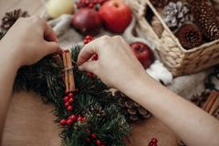 Hands making rustic christmas wreath, holding cinnamon at fir br. Anches, red berries,pine cones,rope, scissors, cotton on rustic wooden background. Atmospheric royalty free stock photos