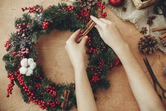 Hands making rustic christmas wreath, holding cinnamon at fir br. Anches, red berries,pine cones,rope, scissors, cotton on rustic wooden background. Atmospheric royalty free stock images