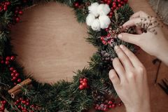 Hands making rustic christmas wreath, holding herbs at fir branches, red berries , pine cones, cotton on rustic wooden background. Atmospheric moody image at stock photography
