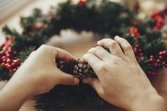 Hands making rustic christmas wreath, holding pine cone at fir b. Ranches, red berries , cotton on rustic wooden background. Atmospheric moody image at winter royalty free stock photo