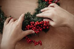 Hands making rustic christmas wreath, holding red berries at fir. Branches, pine cones, cotton on rustic wooden background. Atmospheric moody image at winter royalty free stock photography