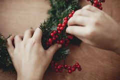 Hands making rustic christmas wreath, holding red berries at fir. Branches, pine cones, cotton on rustic wooden background. Atmospheric moody image at winter stock photos