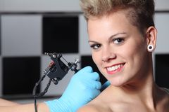 Hands making a tattoo on a woman shoulder. Beautiful woman looking at camera while somebody is making a tattoo on her shoulder royalty free stock images