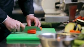 Hands of male chef cook chopping carrot in kitchen stock video