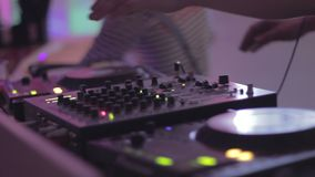Hands of male dj turning controls on sound equipment, playing music in nightclub. Stock footage stock video footage