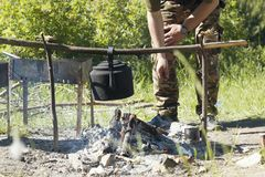 Hands of male hiker cooking on the campfire in summer forest. Horizontal Royalty Free Stock Image