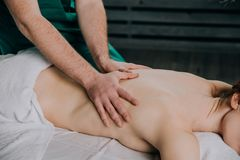 The hands of a male masseur he is doing massage the back of a woman royalty free stock image