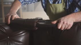 Hands a man in a shirt in a workshop collects an armchair. Hands of a male master work with furniture in a dark authentic workshop stock footage