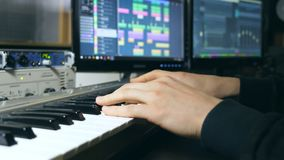 Hands of male musician playing at synthesizer at sound recording studio. Mens arms plays solo of music or new melody stock video footage