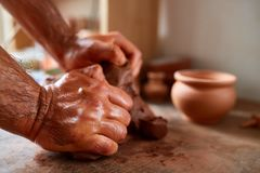 Hands of male potter molding a clay in pottery workshop, close-up, selective focus. Creative work process. Craftsman preparation for making a masterpiece at Royalty Free Stock Photo